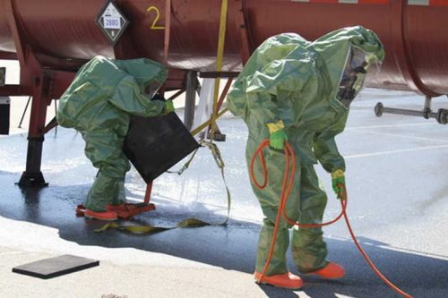 Workers in hazmat suits cleaning up a chemical spill