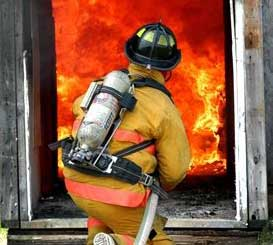 Firefighter putting out a house fire