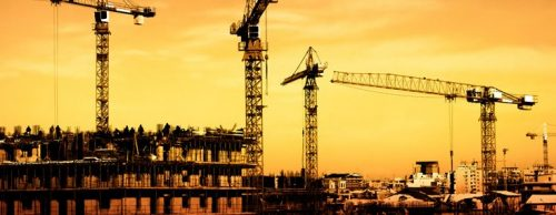 Construction cranes at a large project site