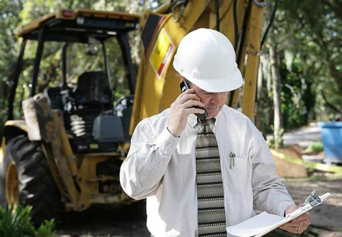 Safety professional talking on the phone in front of an earth mover