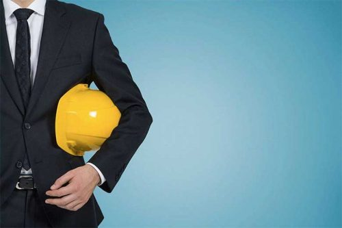 Person in a business suit holding a hard hat