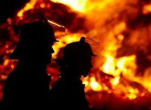 Two firefighters standing in front a fire