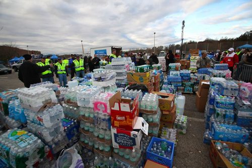 Emergency management professionals standing by crates of water bottles and other disaster relief supplies.