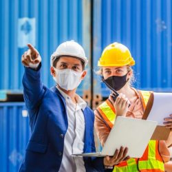 Two safety managers assess workplace hazards in a warehouse.