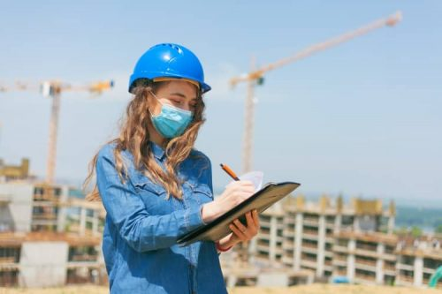 A safety professional is assessing hazards at a large construction site with cranes in the background.