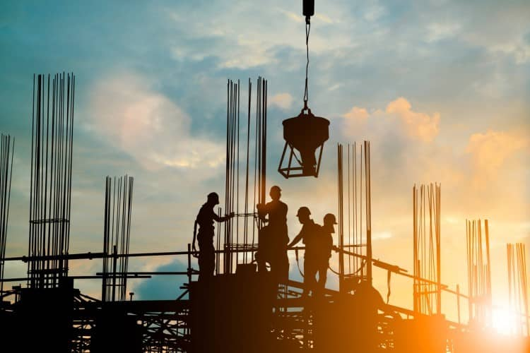 Construction workers stand on a scaffolding, silhouetted against the sky.
