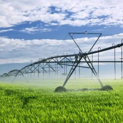 Heavy-duty industrial irrigation equipment spraying grassy farmland