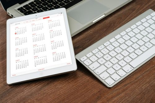 laptop computer, keyboard and calendar on student desk