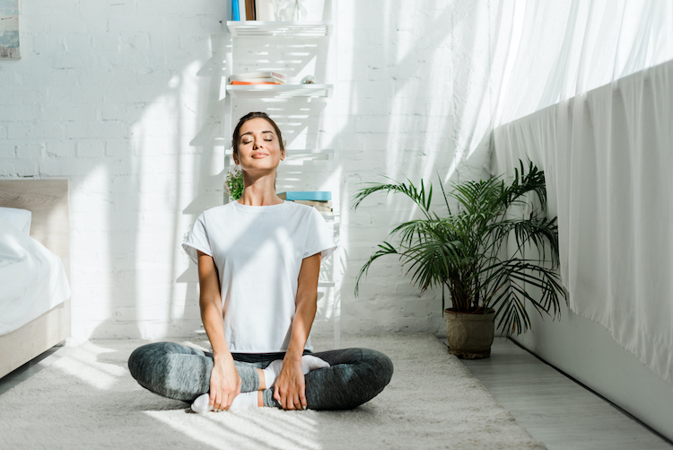 A woman practices meditation in her bedroom.