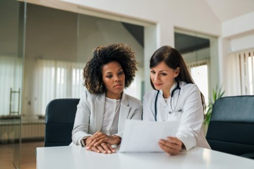 A healthcare administrator and a doctor read a document.