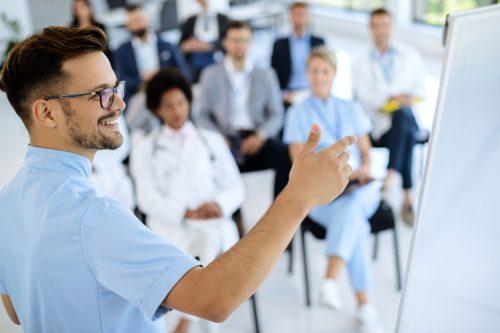 A healthcare entrepreneur gives a presentation to a medical team.
