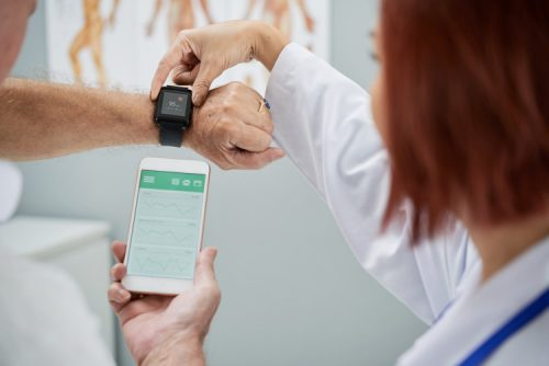 A doctor helps a patient program a wearable device.