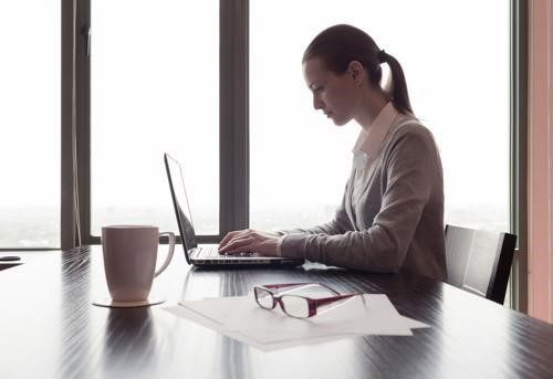 A woman in business attire works on a laptop while sitting at a wooden desk. A mug and a pair of glasses are next to her.