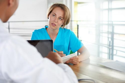 health care worker taking notes from doctor
