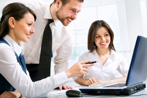 Professionals working around a laptop