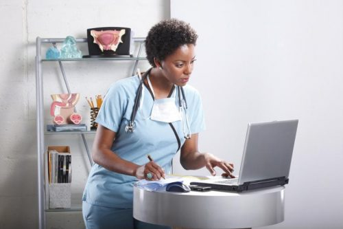 An advanced practice registered nurse works on a laptop