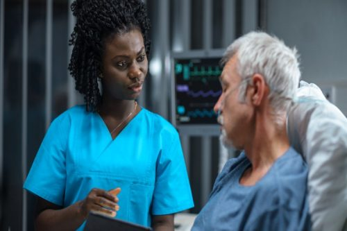 A nurse discusses treatment options with a patient in a hospital bed.