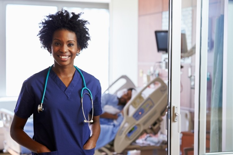 Nurse practitioner standing with a patient in the background.