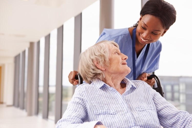 Nurse pushing patient in a wheelchair in a medical office