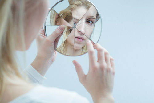 Women looking into cracked mirror
