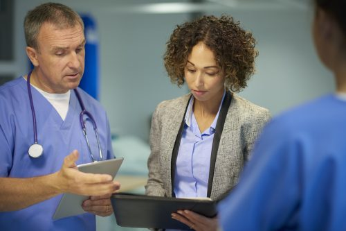 A public health professional works with doctors