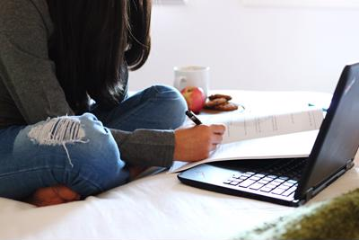 A college student sits on a bed working in a notebook and on a computer.