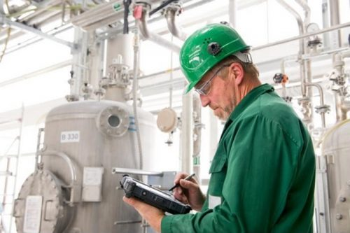 Man in a hard hat in an industrial setting working on a tablet.