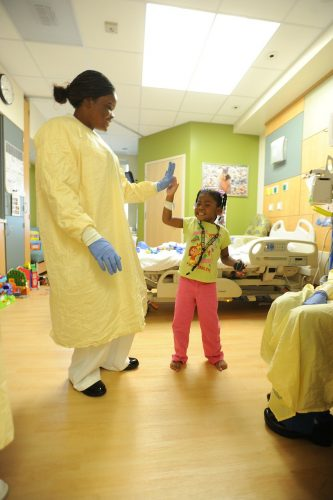 paediatric nurse high fiving young patient