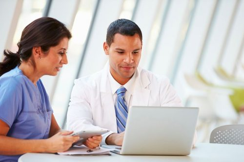 Nurse practitioners working on laptop and tablet