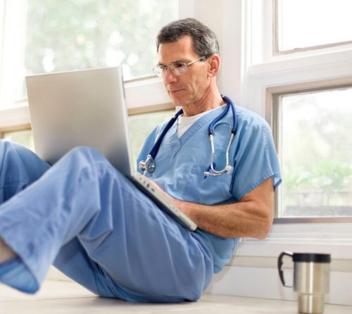 male nurse on laptop while sitting on the ground