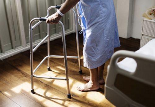 an elderly patient standing using a zimmer frame