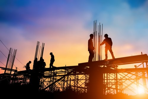 Construction workers walk across scaffolding.