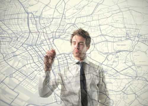 Urban planner drawing on a transparent diagram of a city