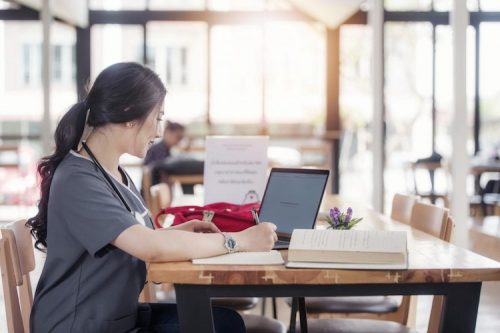 A nurse sits at a table and works on her resume.