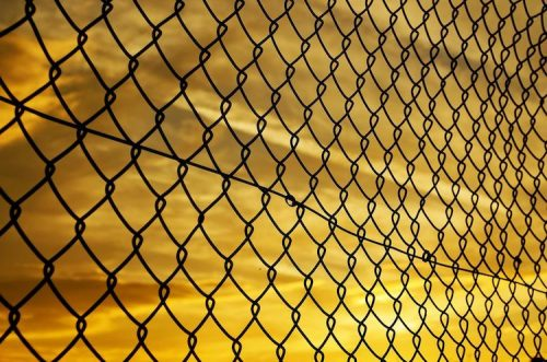 a wire cage fence in front of a yellow sky at sun set