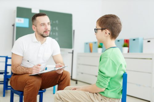 ABA therapist evaluates autistic child patient in a classroom.