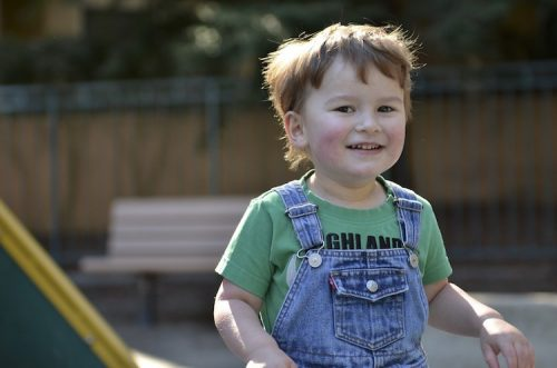 A little boy in overalls smiles at the camera.