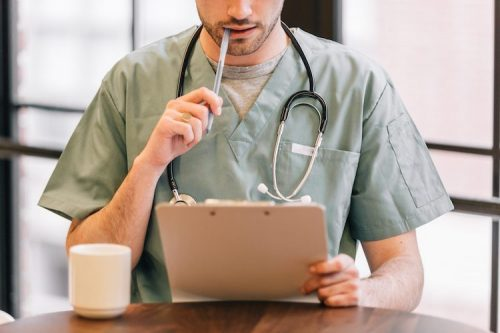 : A nurse looks at documents on a clipboard while sitting at a table.