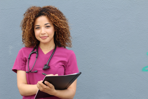 A nurse in purple scrubs poses with a nursing journal.