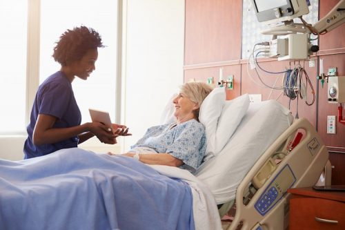 A nurse uses a tablet to gather information from her patient in a hospital bed.