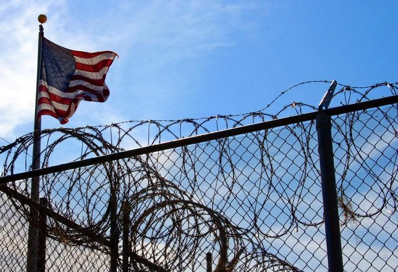 American flag flying over a barbed-wire fence at a correctional facility