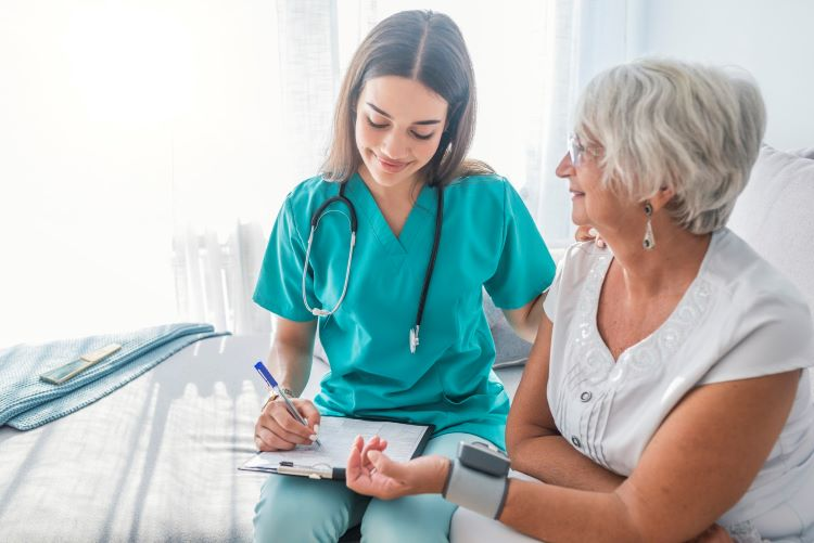 A nurse checks a patient's blood pressure while writing on a medical chart.