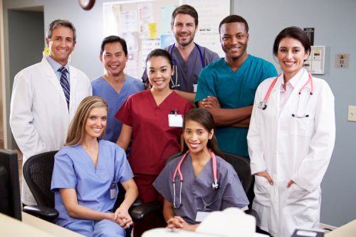 A team of health care professionals poses at a hospital desk.