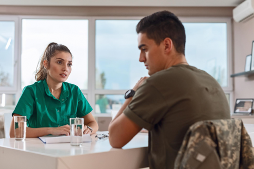 Mental health nurse counsels a depressed military officer with a psychiatric disorder.