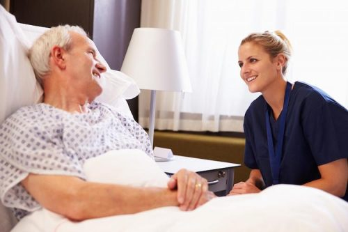 A nurse at the bedside of an elderly patient