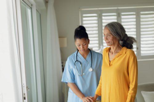 Family nurse practitioner assists elderly woman.