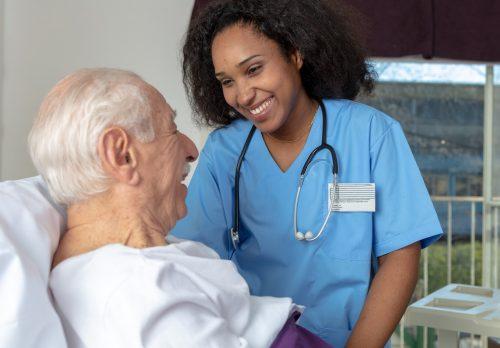 Nurse practitioner assists patient after surgery.