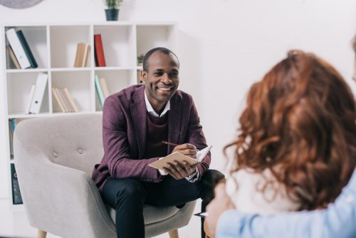 A psychotherapist discusses issues with a patient while sitting in his chair.