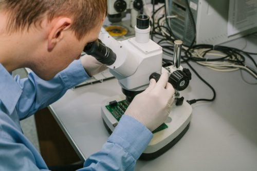 A forensic nurse looks through a microscope.