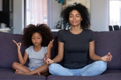 Parent and child practicing yoga relaxation technique